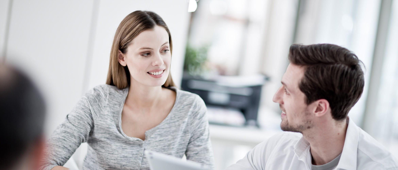 Mann und Frau vor Laptop lächeln, Drucker im Hintergrund