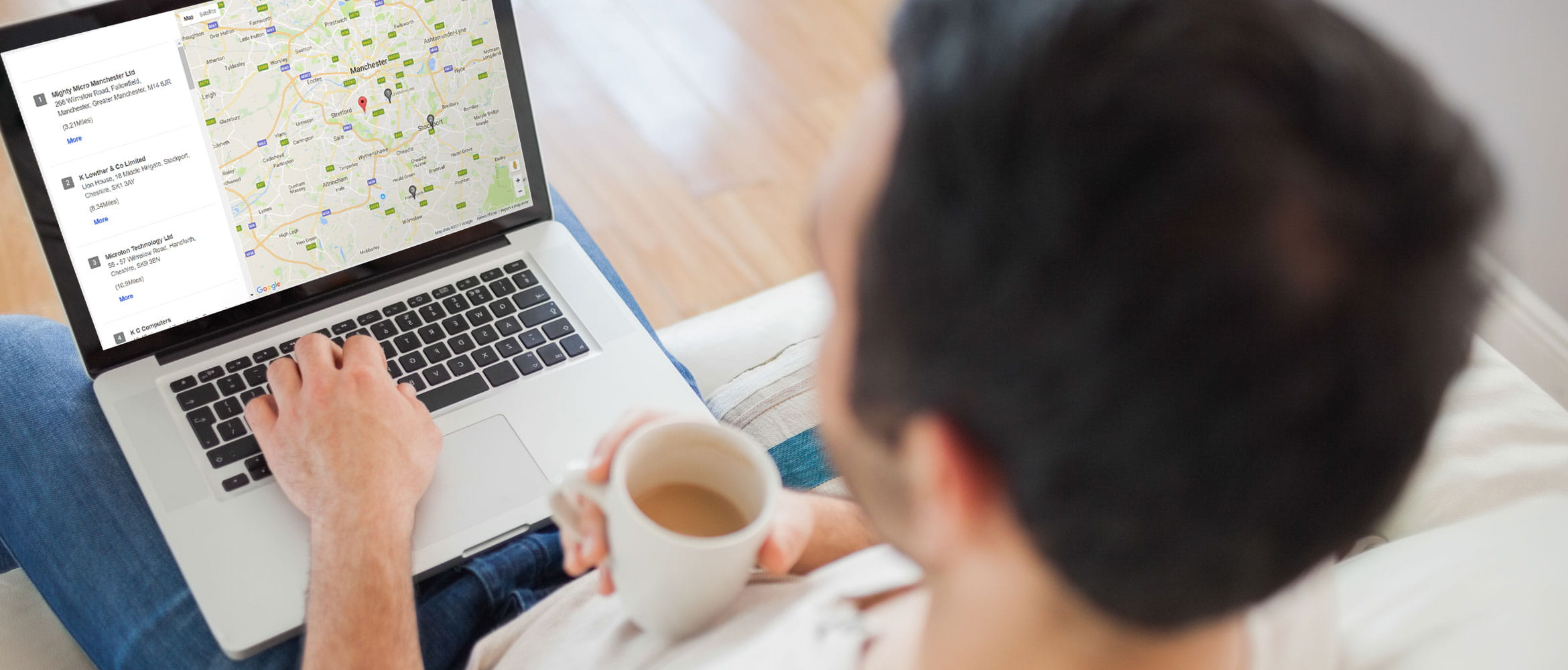 Man sat on a sofa, drinking tea searching for Brother Service Centre on computer
