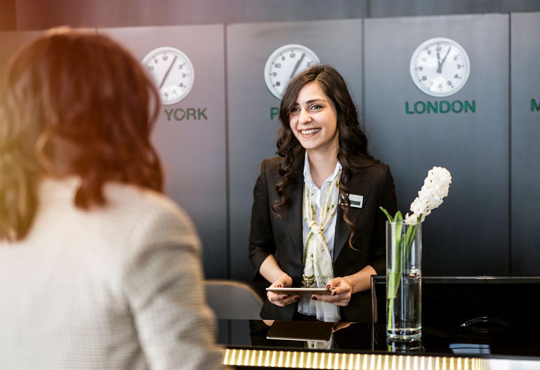 Hotel guest at reception with concierge, clocks, computer, vase