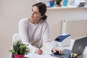 Office worker at her desk looking satisfied with her Brother QL-600B label printer